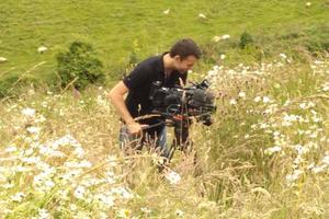 BBC Countryfile's producer films in the meadow area in front of Sharpham House