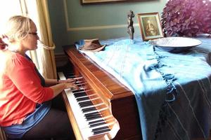 A performer tries the piano in our Music Room