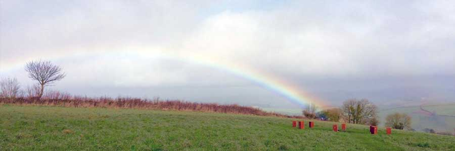 A rainbow over the Fire Circle at Sharpham Meadow Natural Burial Ground